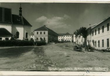 Náměstí městečka Dolní Vltavice. Mezi kostelem a školou je vidět kamenný pranýř. (Johann Mayer, nedatováno, zdroj: soukromá sbírka Jiří a Lenka Hůlkovi)