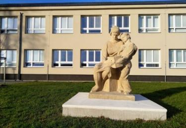 Budova školy se sochou