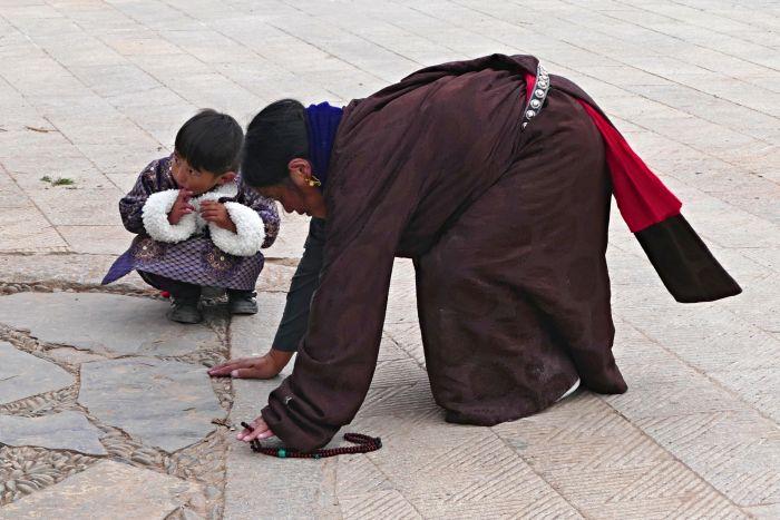 Tibetští poutníci v klášterním komplexu Labrang