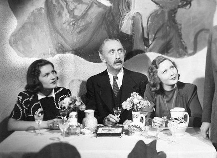 Hodinářka Míla (vlevo), pan domácí Josef Houbička (Jindřich Plachta) a fotografka Lída (Eva Klenová) v komedii U pěti veverek